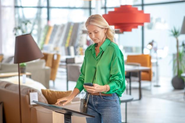 Vrouw met een kleine handtas over haar schouder met een smartphone in haar hand die zich dichtbij een elektronisch apparaat, aandachtig en geconcentreerd zij.