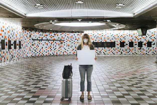 Vrouw met een koffer die een blanco papier vasthoudt tijdens de uitbraak van het coronavirus