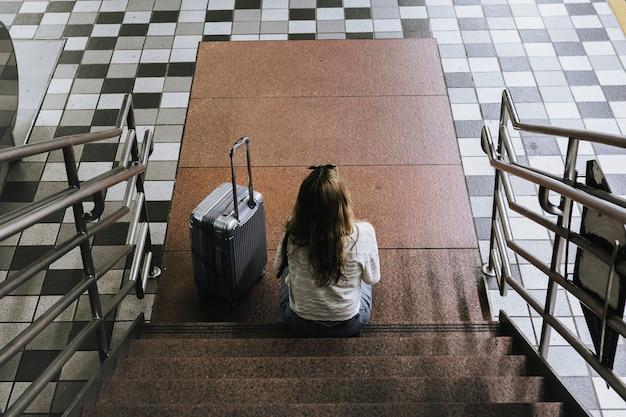 Vrouw met een koffer die op de trap zit te wachten op de trein tijdens de uitbraak van het coronavirus