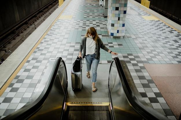 Vrouw met een koffer op een roltrap tijdens de coronaviruspandemie