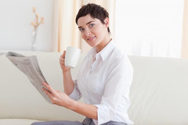 Vrouw met een kop die het nieuws leest terwijl het bekijken de camera