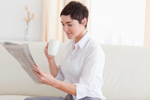 Vrouw met een kop die het nieuws leest