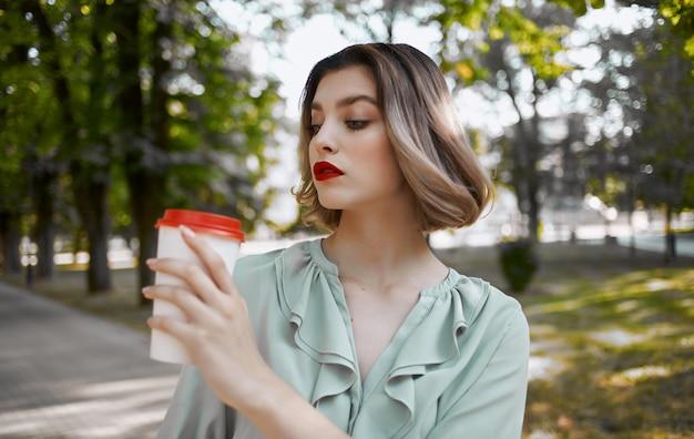 Vrouw met een kopje drankje in de hand loopt in het park in de natuur.