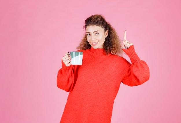 Vrouw met een kopje koffie heeft een idee.
