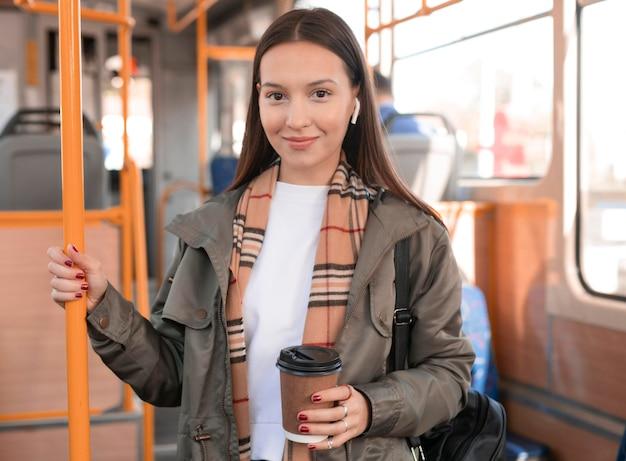 Vrouw met een kopje koffie in het openbaar tramvervoer