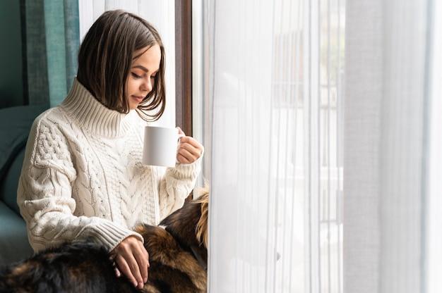 Vrouw met een kopje koffie naast raam thuis tijdens de pandemie