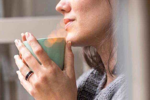 Vrouw met een kopje koffie terwijl ze naar buiten kijkt