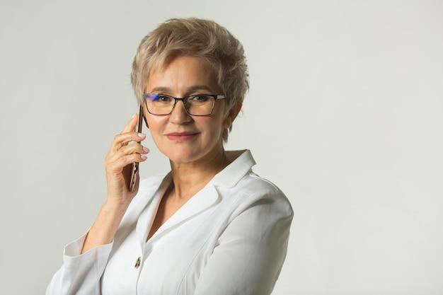Vrouw met een kort kapsel met bril in een wit jasje telefoneert