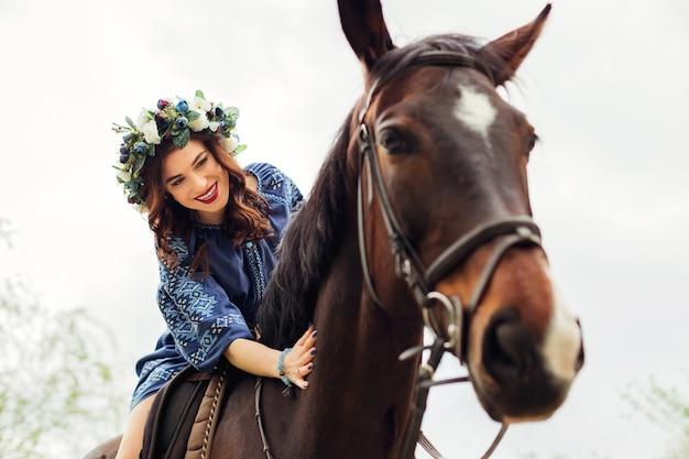 Vrouw met een krans op haar hoofd zittend op een paard en lacht en streelde de nek van een paard