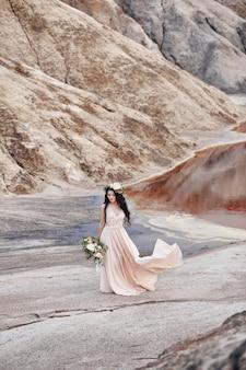 Vrouw met een krans van bloemen op haar hoofd en een boeket mooie bloemen in de hand loopt op een achtergrond van bergen. lange lichte zomerjurk wappert in de wind
