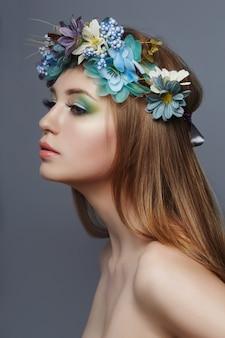 Vrouw met een kroon van blauwe bloemen op haar hoofd