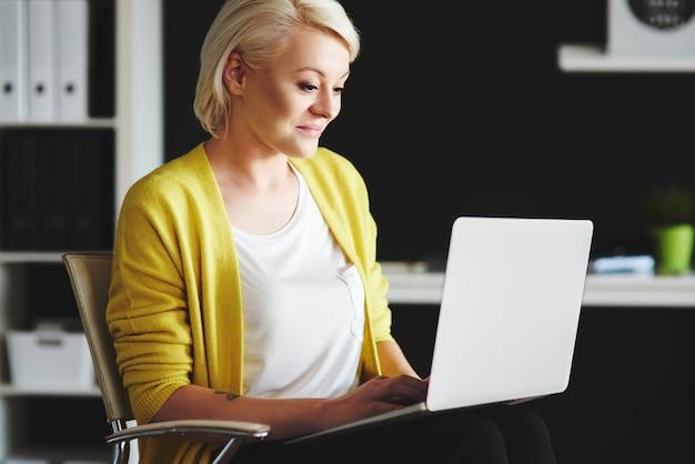 Vrouw met een laptop op de knie aan het chatten