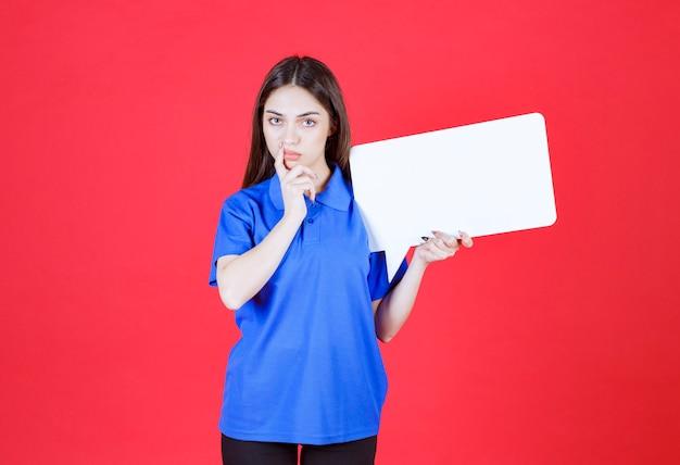 Vrouw met een leeg rechthoekig infobord en ziet er verward en attent uit.