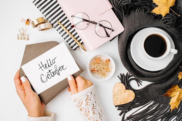 Vrouw met een lege kaart. werkruimte met koffiekopje gewikkeld in sjaal, gouden clips, bril. stijlvol bureau. herfst of winter concept. platliggend, bovenaanzicht