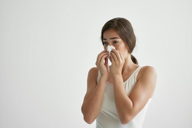 Vrouw met een loopneus veegt haar neus af met een zakdoek verkoudheidsinfectie