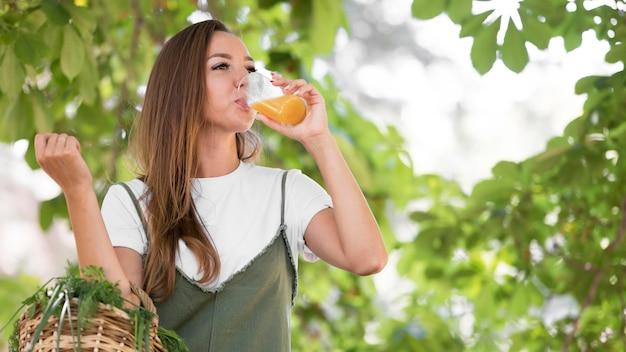 Vrouw met een mand met lekkernijen terwijl ze een sinaasappelsap drinkt