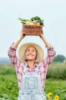 Vrouw met een mand vol oogst biologische groenten en wortel op biologische biologische boerderij. herfst plantaardige oogst.