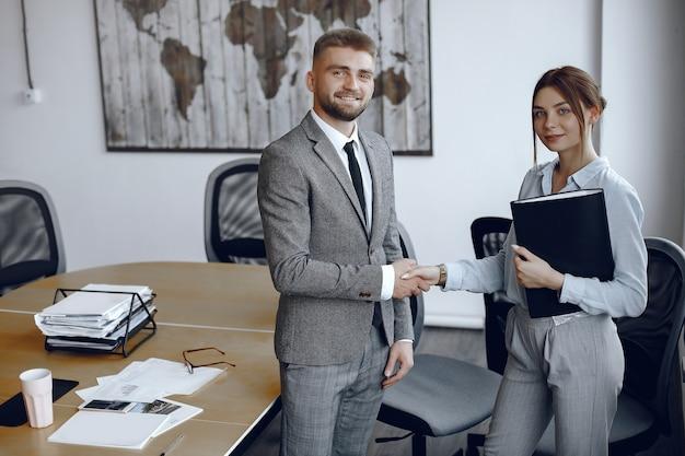 Vrouw met een map in haar handen. zakenman in zijn kantoor. collega's schudden elkaar de hand