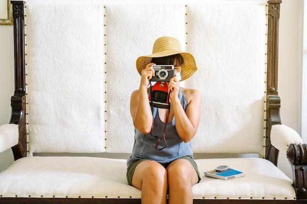 Vrouw met een masker en hoed, zittend in een fauteuil, een foto maken en zich voorbereiden op een reis