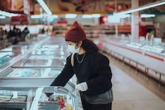 Vrouw met een medisch masker die bevroren voedsel koopt tijdens een pandemie van het coronavirus