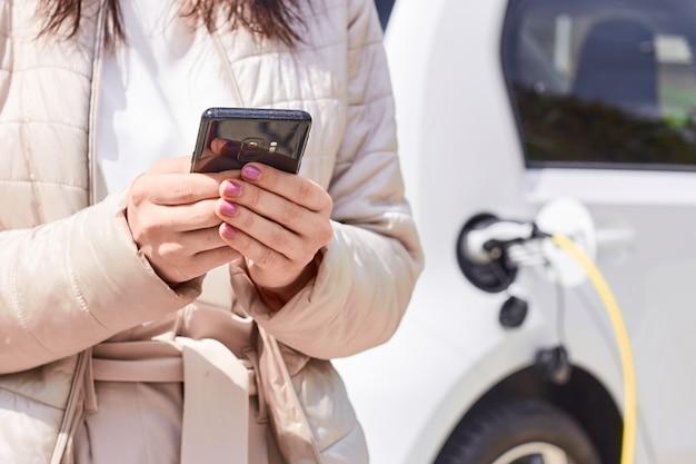 Vrouw met een mobiele telefoon dichtbij het opladen van elektrische auto. voertuig opladen bij openbaar laadstation buitenshuis. autodelen concept