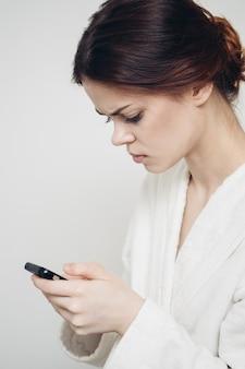 Vrouw met een mobiele telefoon houdt een spons in haar hand tegen een lichte achtergrond.