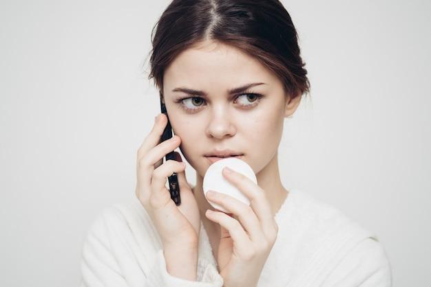 Vrouw met een mobiele telefoon houdt een spons in haar hand tegen een lichte achtergrond