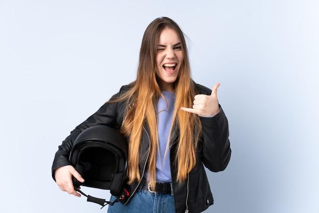 Vrouw met een motorfietshelm die telefoongebaar maakt