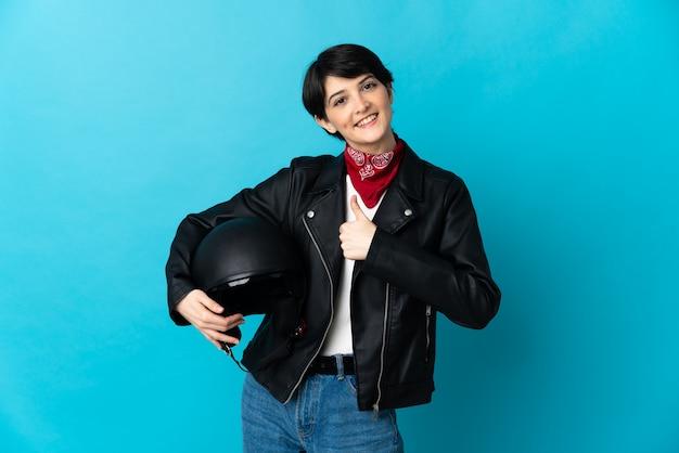 Vrouw met een motorhelm geïsoleerd op blauwe ruimte met een duim omhoog gebaar