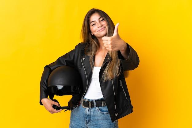 Vrouw met een motorhelm geïsoleerd op gele muur met duimen omhoog omdat er iets goeds is gebeurd
