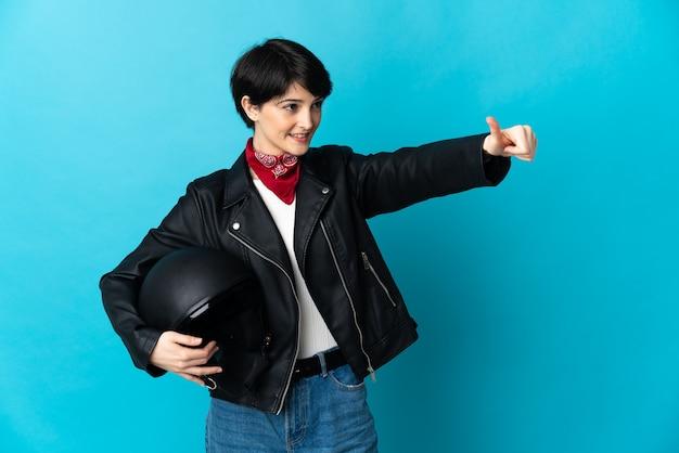 Vrouw met een motorhelm op blauw met een duim omhoog gebaar