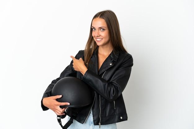 Vrouw met een motorhelm over geïsoleerde witte achtergrond die naar achteren wijst
