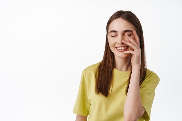 Vrouw met een natuurlijke, frisse schone huid, blozend en kegelvormig gezicht met de hand, gelukkig lachend, staande op wit