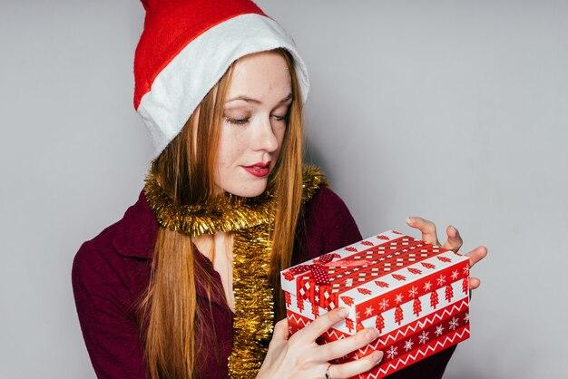 Vrouw met een nieuwjaarshoed houdt een geschenk in haar handen