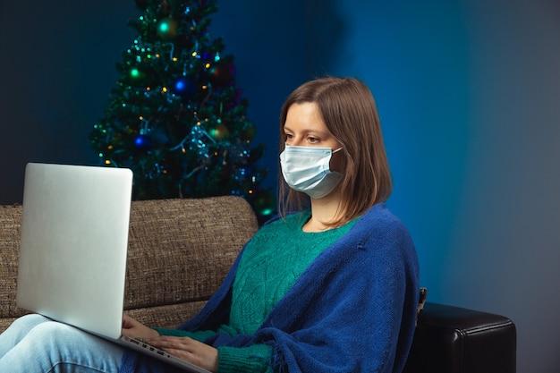Vrouw met een notitieboekje in beschermend gezichtsmasker zittend op de bank met versierde kerstboom