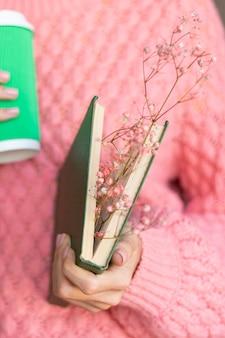 Vrouw met een opengeslagen boek met een boeket gedroogde bloemen erin en een papieren kopje koffie