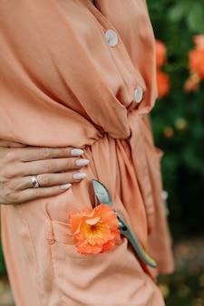 Vrouw met een oranje roos en een tuinschaar