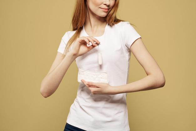 Vrouw met een pad in haar handen, maandverband en tampons