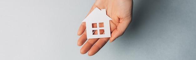 Vrouw met een papieren huis met haar handen met de zon op een lichtblauwe ruimte
