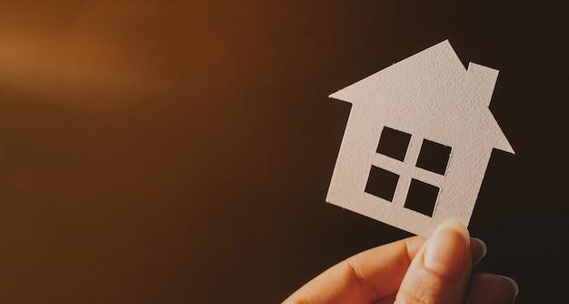 Vrouw met een papieren huis met haar handen verlicht op een donkere ruimte