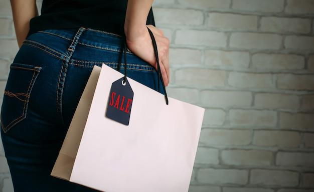 Vrouw met een papieren zak met black friday-tag
