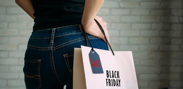 Vrouw met een papieren zak met label black friday. achteraanzicht van slanke vrouwelijke kont in spijkerbroek