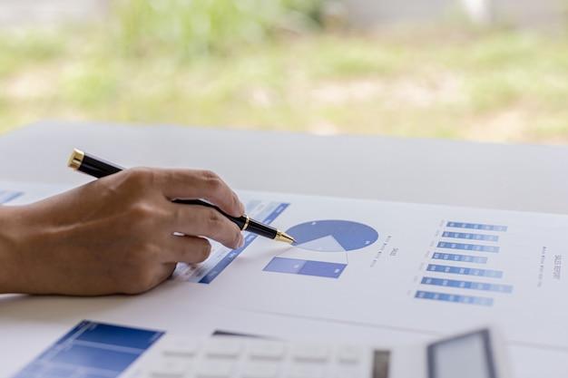 Vrouw met een pen die naar documenten op een bureau wijst, ze is een financiële geleerde, ze controleert de financiële documenten van het bedrijf op juistheid voordat ze ze aan leidinggevenden presenteert. financieel auditconcept.
