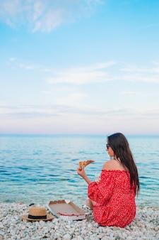 Vrouw met een picknick met pizza op het strand