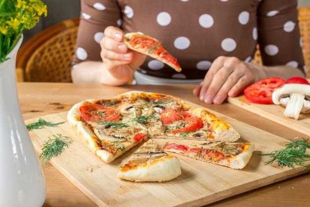 Vrouw met een plak van een eigengemaakte rechthoekige pizza margherita met paddestoelen.