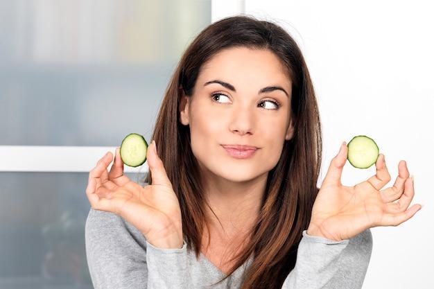 Vrouw met een plakje komkommer in de keuken