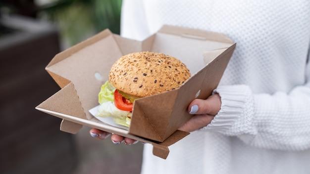 Vrouw met een recyclebare papieren voedseldoos met een sandwich. recycling idee
