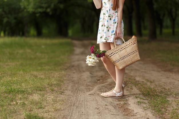 Vrouw met een rieten mand en bloemen op een landweg.