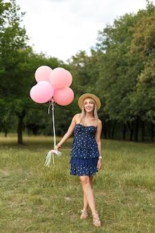 Vrouw met een rieten mand, hoed, roze impulsen en bloemen die op een landweg lopen