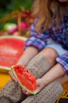 Vrouw met een rijp stuk van watermeloen in een hand op een herfstpicknick